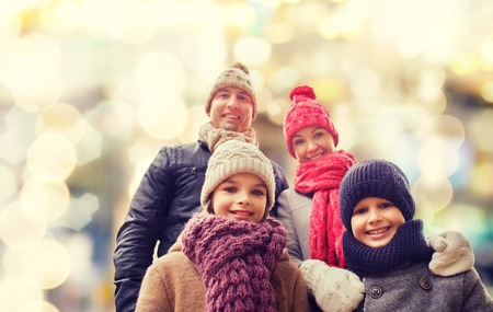 Photo for family, childhood, season, holidays and people concept - happy family in winter clothes over lights background - Royalty Free Image