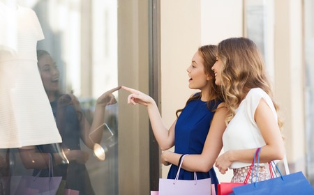 Foto de sale, consumerism and people concept - happy surprised young women with shopping bags pointing finger to shop window outdoors - Imagen libre de derechos