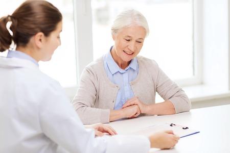 Foto de medicine, age, health care and people concept - doctor with clipboard and senior woman meeting at hospital - Imagen libre de derechos