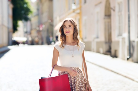 Photo for sale, consumerism and people concept - happy young woman with shopping bags walking along city street - Royalty Free Image