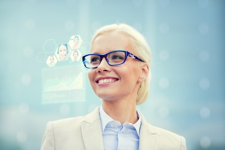 Foto de business, people, future technology and communication concept - young smiling businesswoman in eyeglasses with virtual screen, video chat and charts projection outdoors - Imagen libre de derechos