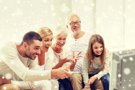 Foto de family, happiness, generation and people concept - happy family sitting on sofa and watching tv at home - Imagen libre de derechos