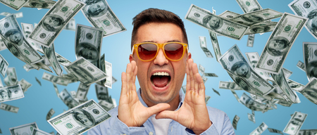 Foto de business, finance, emotions, and people concept - face of angry middle aged latin man in shirt and sunglasses shouting over blue background with heap of falling dollar money - Imagen libre de derechos