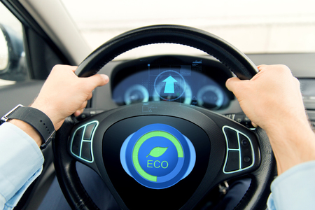 Foto de transport, business trip, technology and people concept - close up of male hands holding car wheel and driving in eco mode - Imagen libre de derechos