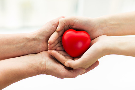 Foto de people, age, family, love and health care concept - close up of senior woman and young woman hands holding red heart - Imagen libre de derechos