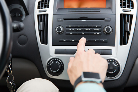 Photo for transport, road trip, car driving, technology and people concept - close up of male hand turning on radio on control panel system in car - Royalty Free Image