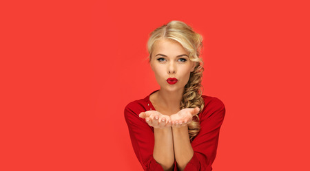 Photo for people, holidays, christmas, valentines day and advertisement concept - lovely woman in red dress blowing something on palms of her hands over red background - Royalty Free Image