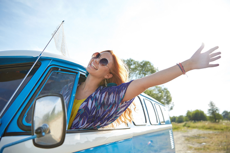 Photo pour summer holidays, road trip, vacation, travel and people concept - smiling young hippie woman driving minivan car and waving hand - image libre de droit