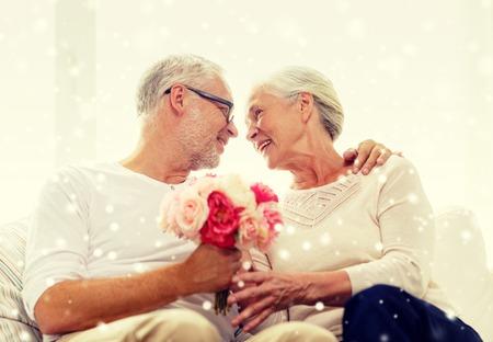 Foto de family, holidays, age and people concept - happy senior couple with bunch of flowers at home - Imagen libre de derechos