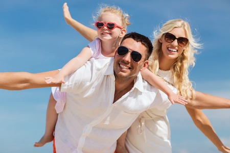 Photo pour family, summer vacation, adoption and people concept - happy man, woman and little girl in sunglasses having fun over blue sky background - image libre de droit