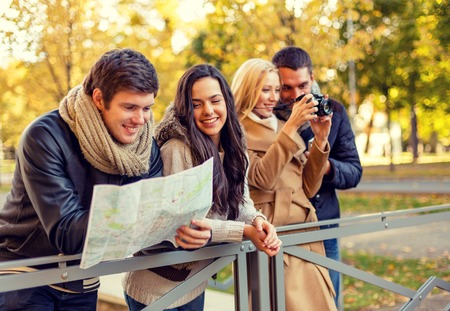 Foto de travel, vacation, technology, tourism and friendship concept - group of smiling friends with digital photo camera and map in city park - Imagen libre de derechos