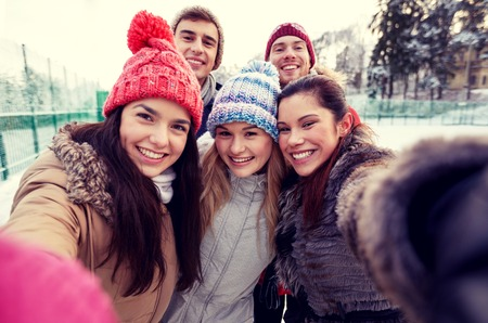 Photo pour people, friendship, technology, winter and leisure concept - happy friends taking selfie with smartphone or camera outdoors - image libre de droit