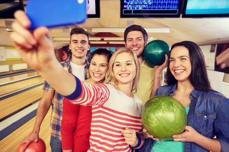 Photo pour people, leisure, sport, friendship and entertainment concept - happy friends taking selfie with smartphone in bowling club - image libre de droit