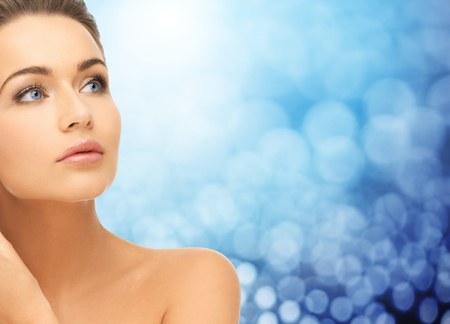 beauty, people and health concept - beautiful young woman face and bare shoulder over blue lights background