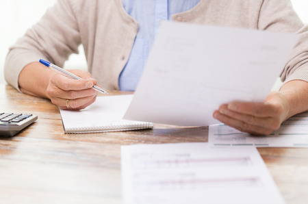 Foto de business, savings, annuity insurance, age and people concept - senior woman with papers or bills and calculator writing at home - Imagen libre de derechos
