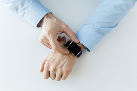 Foto per business, technology and people concept - close up of male hands setting smart watch at home - Immagine Royalty Free