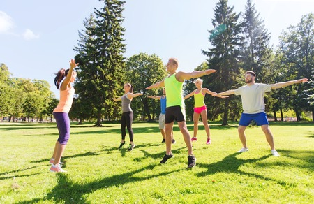 Foto de fitness, sport, friendship and healthy lifestyle concept - group of happy teenage friends exercising at boot camp - Imagen libre de derechos