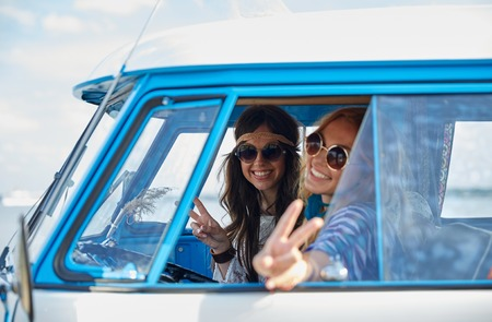 Photo pour summer holidays, road trip, vacation, travel and people concept - smiling young hippie women driving minivan car and showing peace gesture - image libre de droit