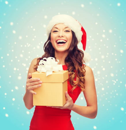 Photo for christmas, x-mas, new year, winter, happiness concept - smiling woman in santa helper hat with gift box - Royalty Free Image