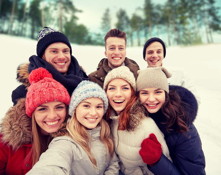 Photo pour winter, technology, friendship and people concept - group of smiling men and women taking selfie outdoors - image libre de droit