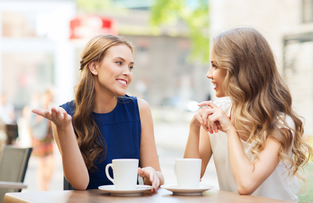 Foto de people, communication and friendship concept - smiling young women drinking coffee or tea and talking at outdoor cafe - Imagen libre de derechos