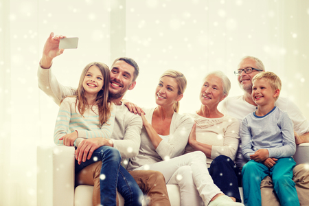 Photo pour family, technology, generation and people concept - happy family sitting on couch and making selfie with smartphone at home - image libre de droit