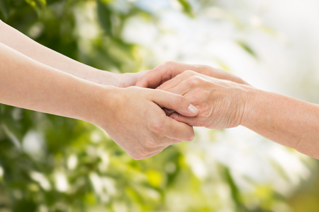 Foto de people, age, family, care and support concept - close up of senior woman and young woman holding hands over green natural background - Imagen libre de derechos