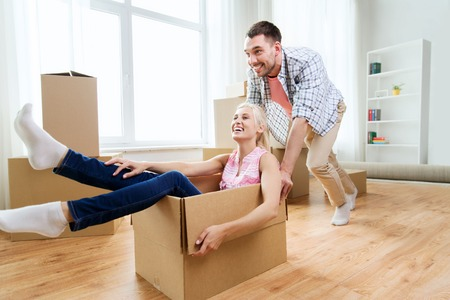 Photo for home, people, moving and real estate concept - happy couple having fun and riding in cardboard boxes at new home - Royalty Free Image
