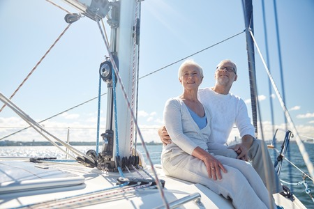 Photo pour sailing, age, tourism, travel and people concept - happy senior couple hugging on sail boat or yacht deck floating in sea - image libre de droit