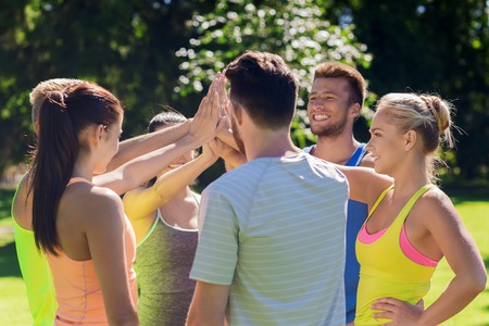 Photo pour fitness, sport, friendship and healthy lifestyle concept - group of happy teenage friends or sportsmen making high five outdoors - image libre de droit