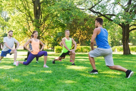 fitness, sport, friendship and healthy lifestyle concept - group of happy teenage friends or sportsmen exercising and doing lunge at boot camp