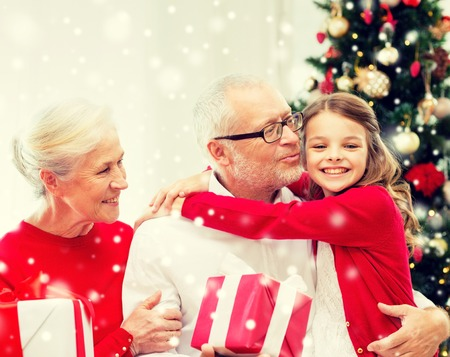 Foto per family, holidays, generation, christmas and people concept - smiling grandparents and granddaughter with gift boxes sitting on couch at home - Immagine Royalty Free
