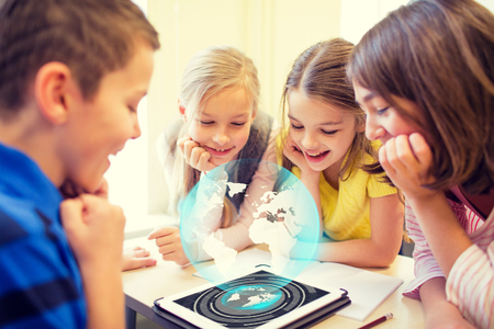 Photo for education, elementary school, learning, technology and people concept - group of school kids looking to tablet pc computer screen with globe hologram on break in classroom - Royalty Free Image