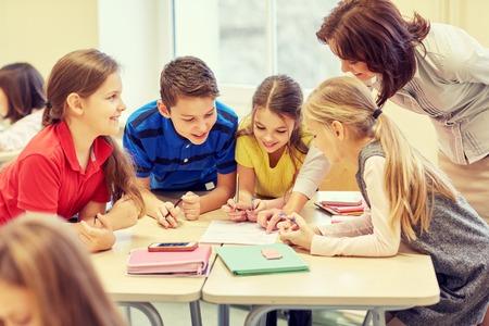 Foto de education, elementary school, learning and people concept - teacher helping school kids writing test in classroom - Imagen libre de derechos