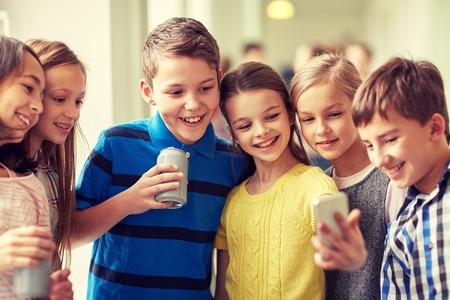 Photo for education, elementary school, drinks, children and people concept - group of school kids with smartphone and soda cans taking selfie in corridor - Royalty Free Image