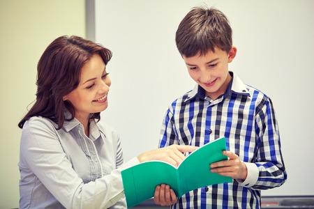 Foto de education, elementary school, learning, examination and people concept - school boy with notebook and teacher in classroom - Imagen libre de derechos