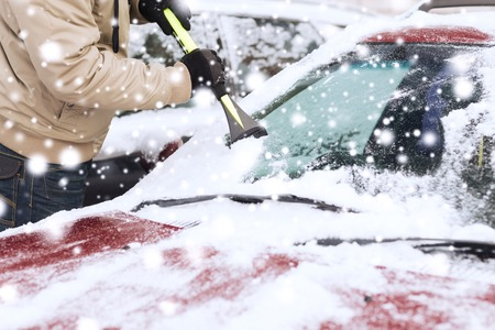Foto de transportation, winter, weather, people and vehicle concept - closeup of man cleaning snow from car windshield with brush - Imagen libre de derechos