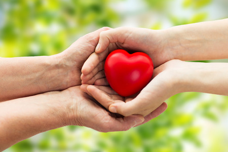 Photo pour people, age, family, love and health care concept - close up of senior woman and young woman hands holding red heart over green natural background - image libre de droit