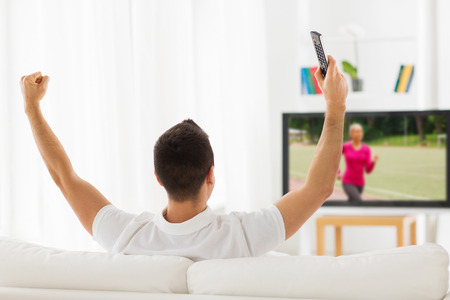 Photo for leisure, technology, mass media and people concept - man with remote control watching sport channel on tv and supporting at home from back - Royalty Free Image
