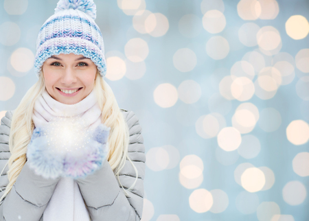 Foto de season, christmas, holidays and people concept - smiling young woman in winter clothes over lights background - Imagen libre de derechos