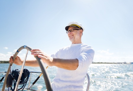 Foto de sailing, age, tourism, travel and people concept - happy senior man in captain hat on steering wheel and navigating sail boat or yacht floating in sea - Imagen libre de derechos