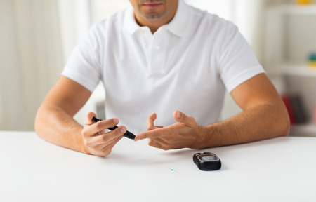 Foto per medicine, diabetes, glycemia, health care and people concept - close up of man checking blood sugar level by glucometer at home - Immagine Royalty Free