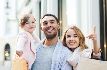 Photo for sale, consumerism and people concept - happy family with little child and shopping bags in city - Royalty Free Image