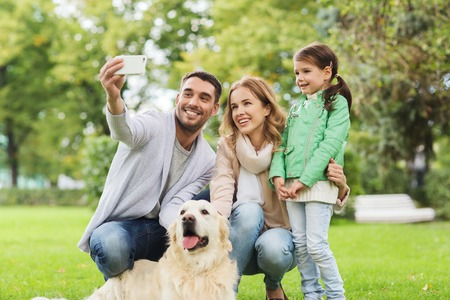 Foto de family, pet, animal, technology and people concept - happy family with labrador retriever dog taking selfie by smartphone in park - Imagen libre de derechos