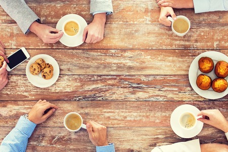 Foto de business, people and team work concept - close up of creative team meeting and drinking coffee during lunch in office - Imagen libre de derechos