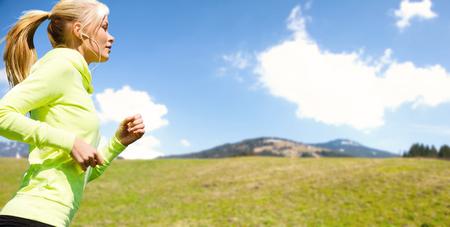 Foto de people, fitness, sport and healthy lifestyle concept - happy sporty woman running or jogging over nature - Imagen libre de derechos