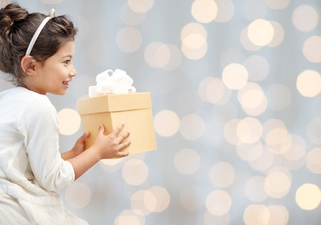 Photo for holidays, presents, christmas, childhood and people concept - smiling little girl with gift box over lights background - Royalty Free Image