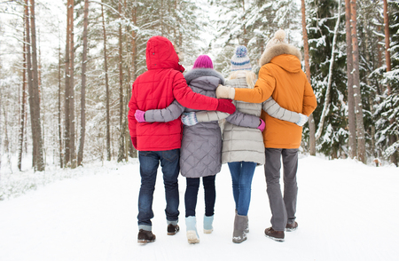 Photo pour love, relationship, season, friendship and people concept - group of happy men and women walking in winter forest - image libre de droit
