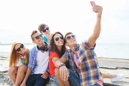 Photo for friendship, leisure, summer, technology and people concept - group of happy friends with smartphone taking selfie outdoors - Royalty Free Image