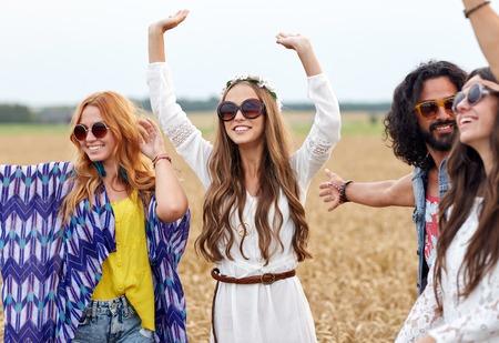 Foto de nature, summer, youth culture and people concept - happy young hippie friends dancing on cereal field - Imagen libre de derechos